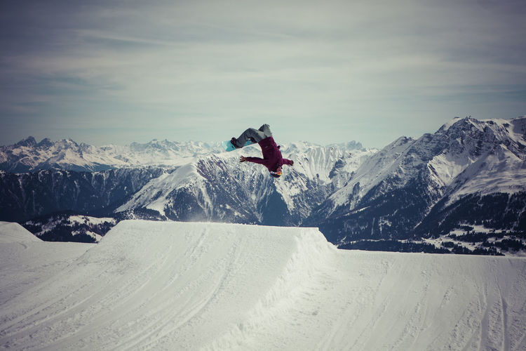 Snowboarder jumping against sky at mountain