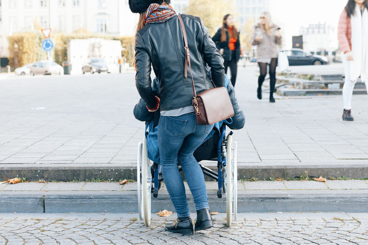 Rear view of woman assisting man sitting in wheelchair