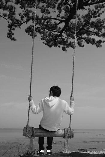 Rear view of man swinging at beach