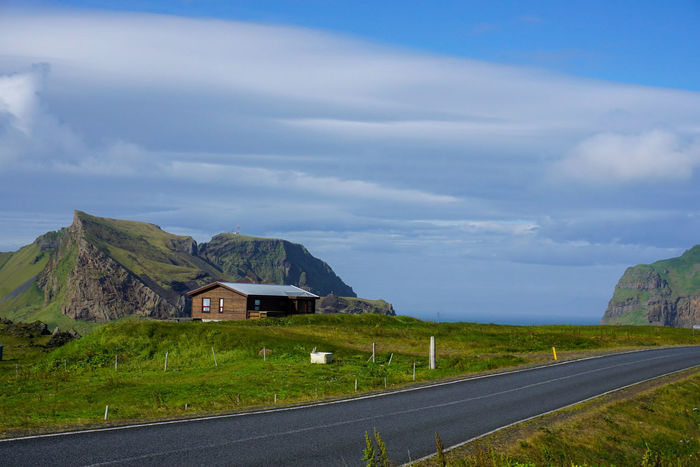 Heimaey Cliffs Island Iceland Vestmannaeyjar Road Hitchhiking Backpacking Remote Remote House Driving Around Roadtrip Nature Beauty In Nature Summer Coast Blue Sky Rural Scene Mountain Road House Sky Architecture Building Exterior Built Structure Agricultural Building Hut Farmhouse Village Cottage
