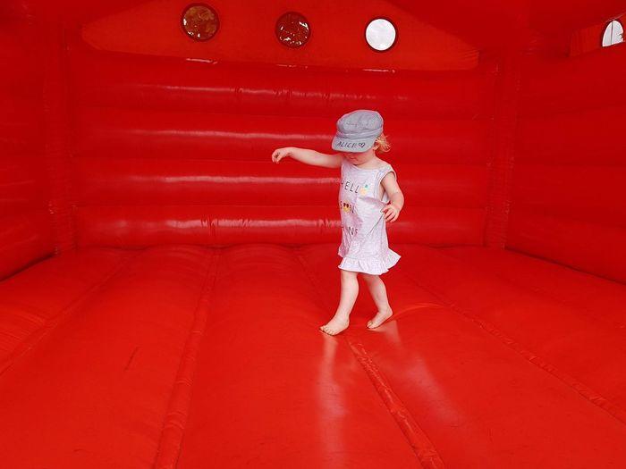 Full length of girl playing on red bouncy castle