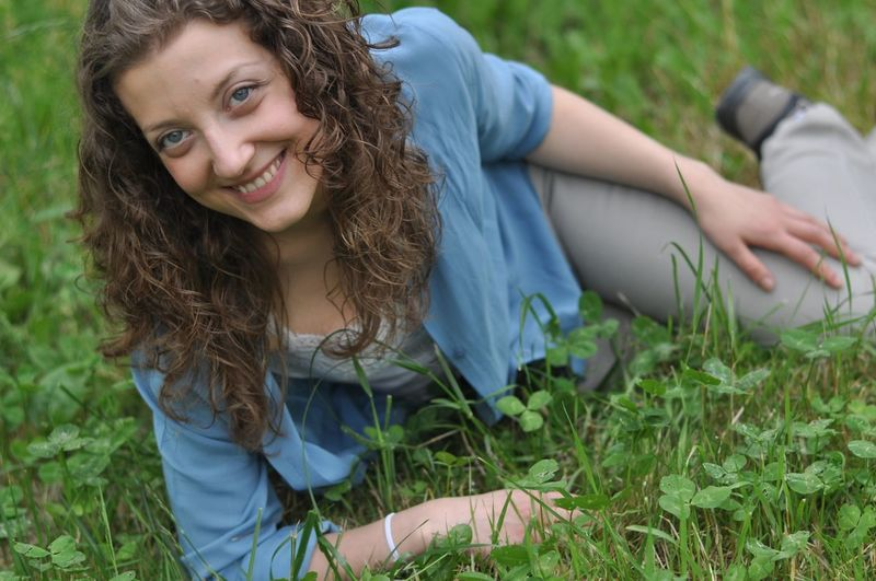Portrait of happy woman sitting on grass