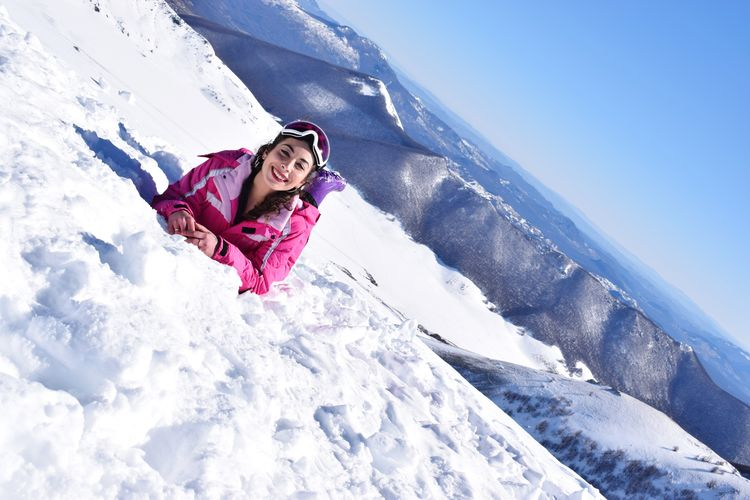 Portrait of smiling woman lying on snowcapped mountain against clear blue sky