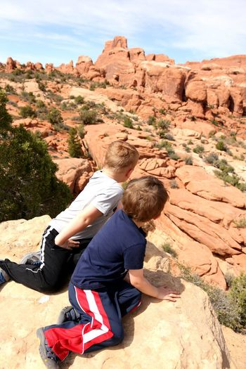 Brothers sitting on rock at desert