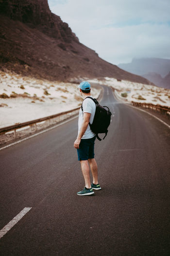 Side View Of Man With Backpack On Road