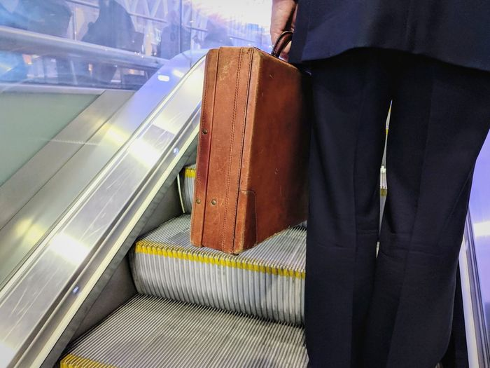 Mid section of business man standing on escalator carrying a leather business case