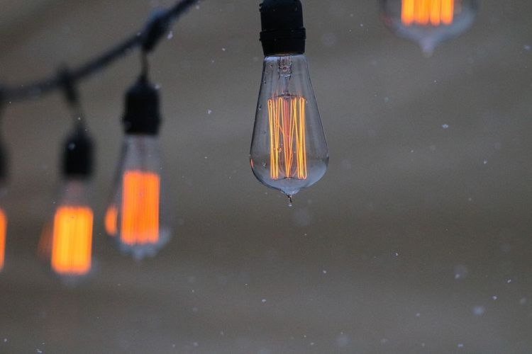Close-up of illuminated light bulb hanging over water