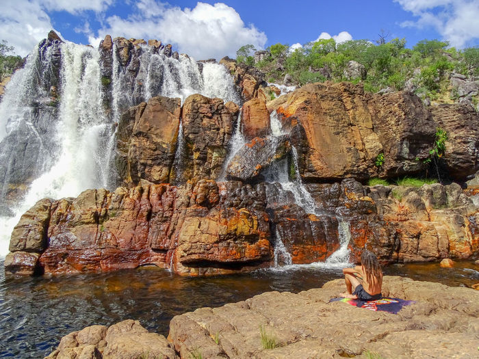 Man sitting on rock formations against waterfall