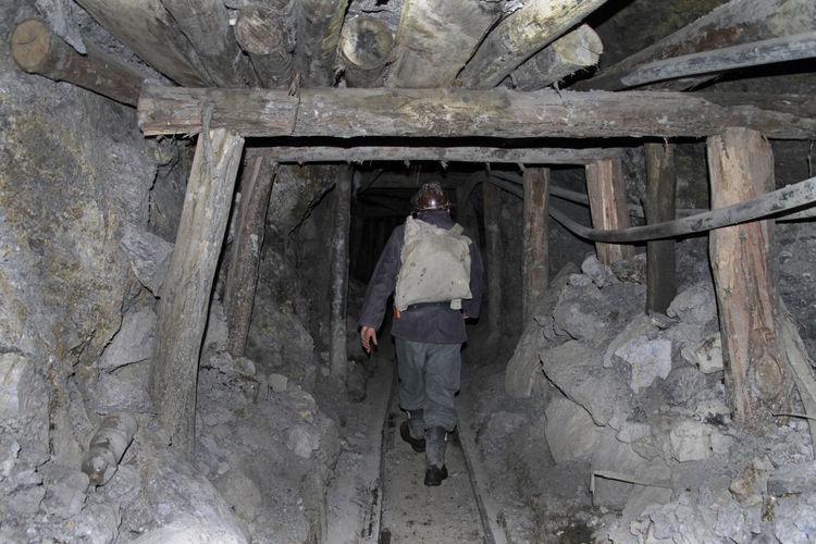 Rear view of worker walking in tunnel