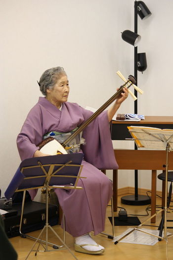 Japan Chair Classical Music Classroom Day Education Full Length Happiness Holding Human Hand Indoors  Men Music Musical Instrument Musician One Person People Real People Senior Adult Shamisen Sitting Skill