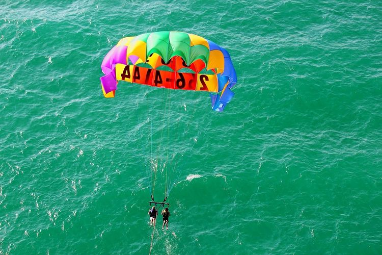 High angle view of people paragliding over sea