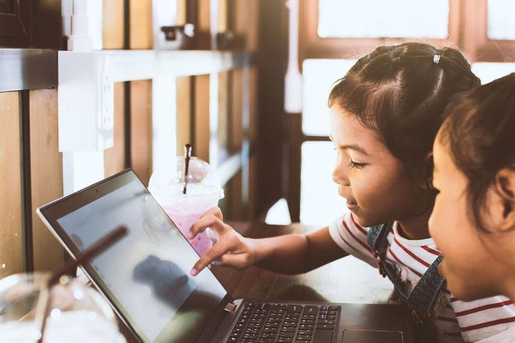 Schoolgirls Using Laptop In Classroom