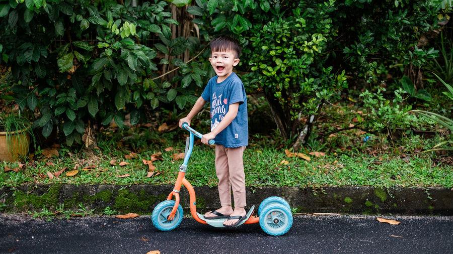 Portrait of smiling boy standing against plants