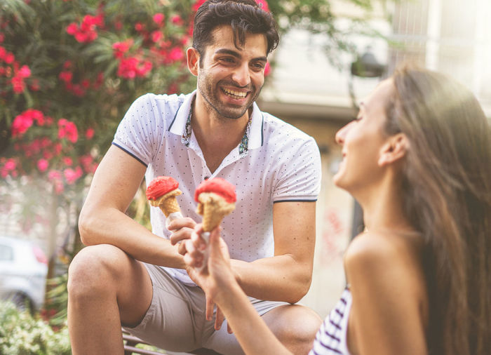 Happy couple holding ice cream cones in park
