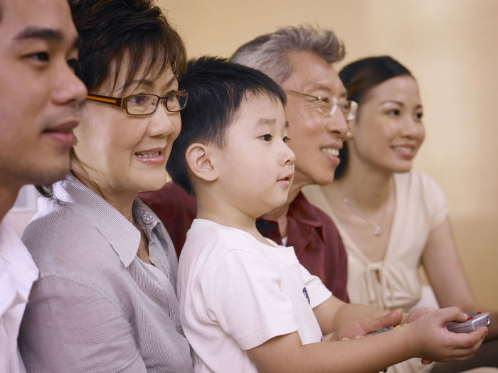 Multi-Generation Family Watching Tv While Sitting At Home