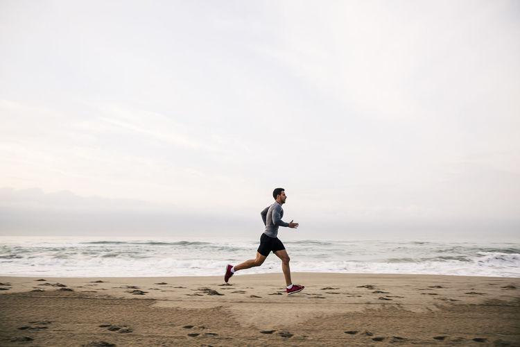 Full length of man running on beach against sky