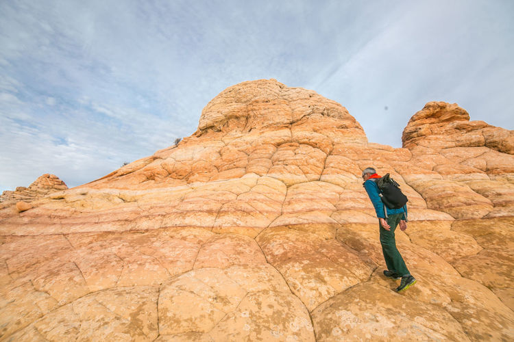 Full length of man on rock formation against sky