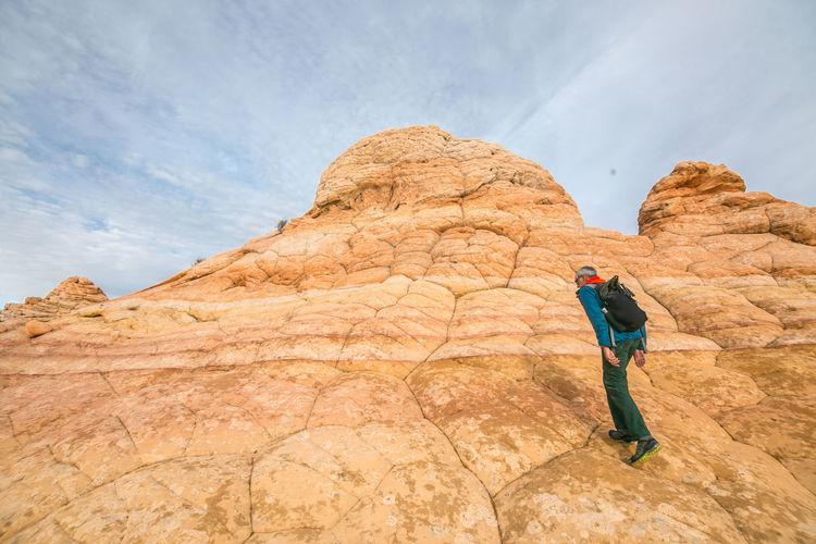 Full length of man on rock formation against sky