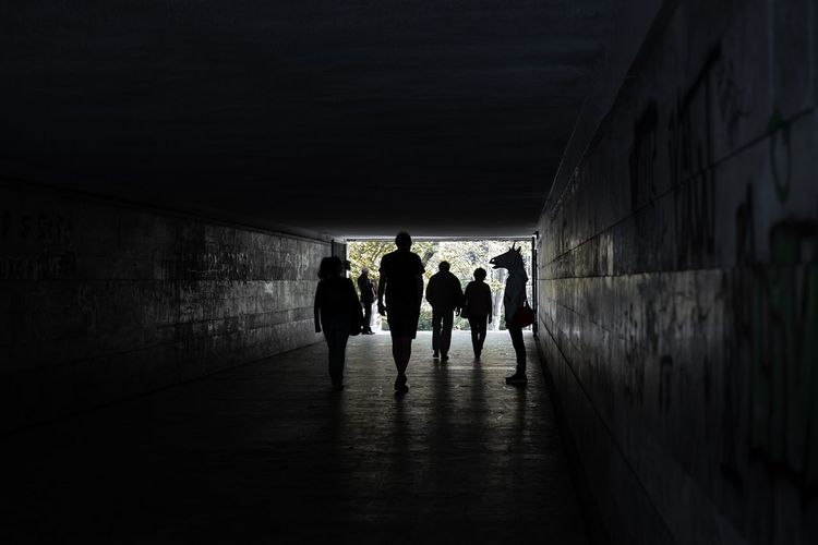 Silhouette people walking in tunnel