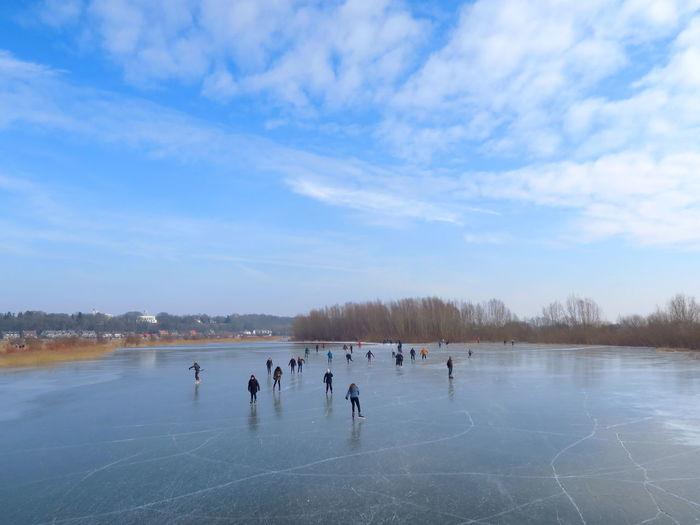 People Skating On Ice Rink Against Blue Sky