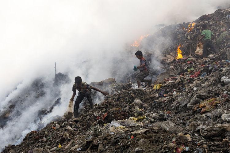 Boys on garbage burning at junkyard