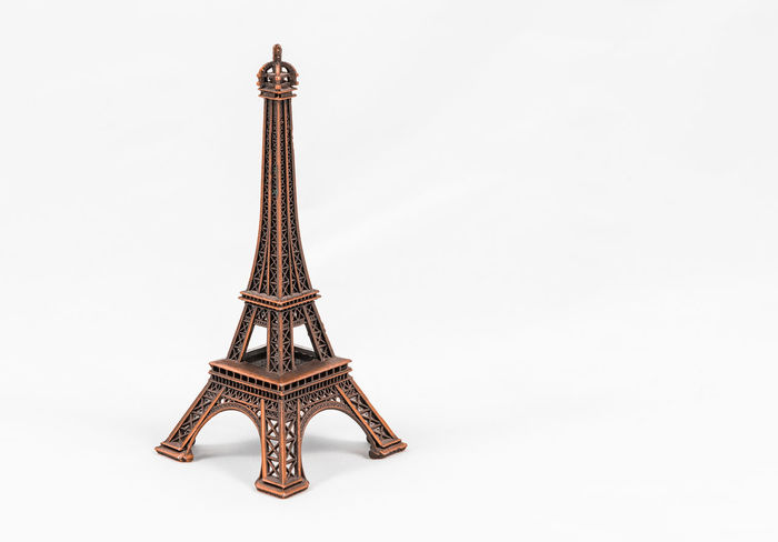 Close up shot of a bronze miniature model of the Eiffel Tower isolated on a white background, with copy space Antique Architecture Art And Craft Close-up Copy Space Craft Cut Out Indoors  Metal No People Ornament Ornate Pattern Silver Colored Single Object Souvenir Studio Shot White Background