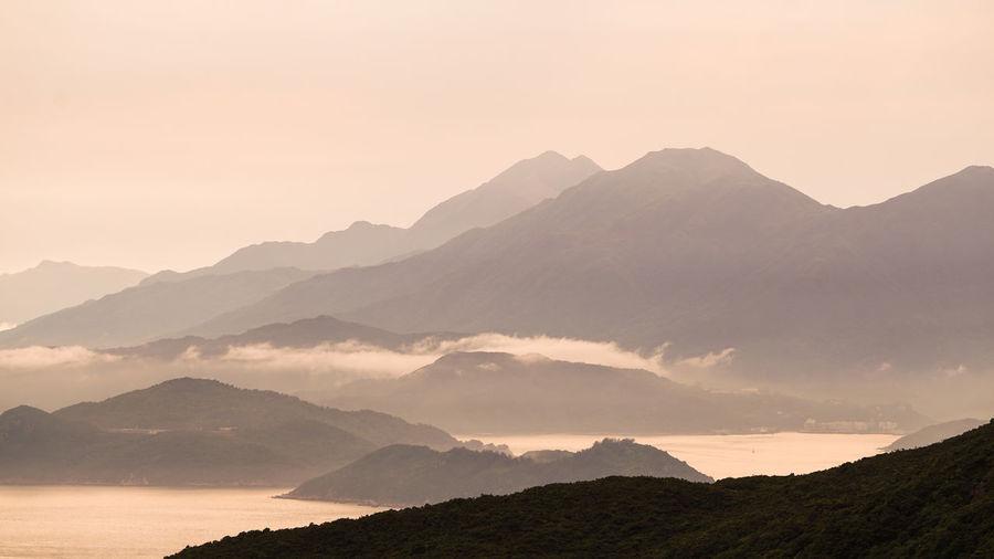 Hong kong cargo ship nuatical transportation  vessel ocean beautiful sunset mountain landscape