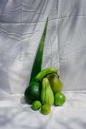 High angle view of green chili peppers on bed