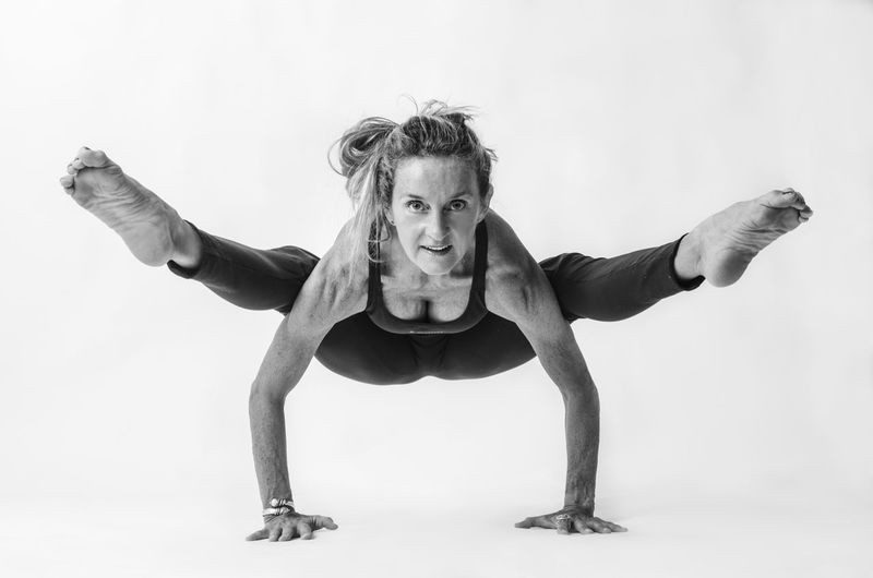 Yoga Adult Balance Confidence  Exercising Front View Full Length Healthy Lifestyle Human Arm Indoors  Lifestyles Looking At Camera One Person Portrait Sport Strength Studio Shot Vitality