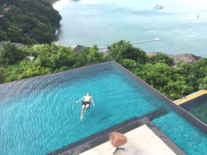High Angle View Of Man Swimming In Infinity Pool