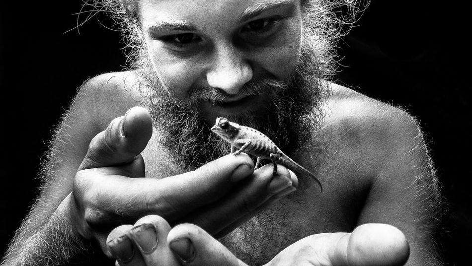 Man with chameleon. Black Background Casual Clothing Chameleon Close-up Conservation Focus On Foreground Hairy  Headshot Human Face Leisure Activity Lifestyles Man Nature NOMAD Part Of Portrait Studio Shot Tribe Wild