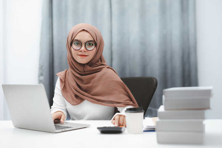 Midsection of woman using phone while sitting on table