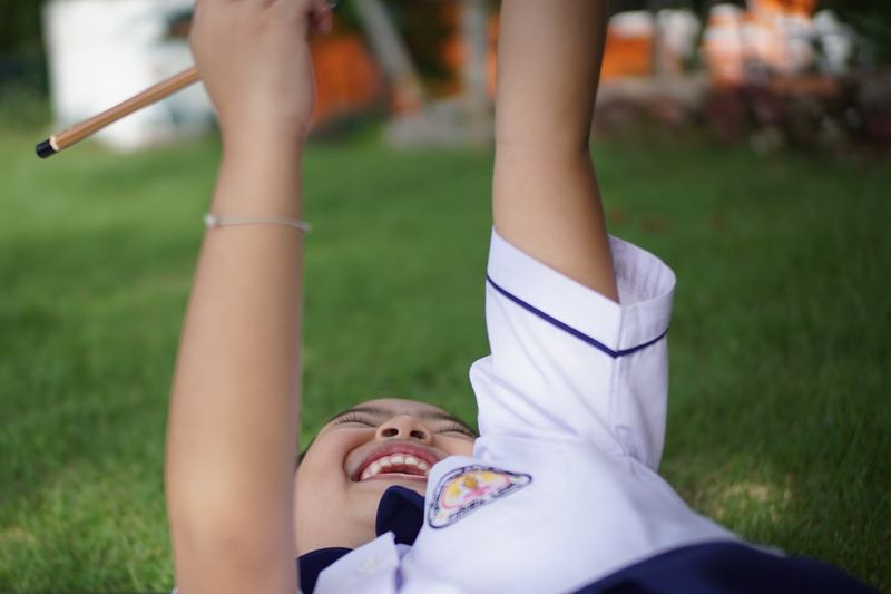 Cheerful Girl Wearing School Uniform While Playing On Field