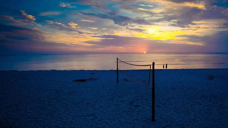 Volleyball net at beach against sky during sunset