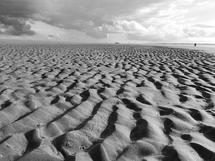 Footprints on sand at beach against sky