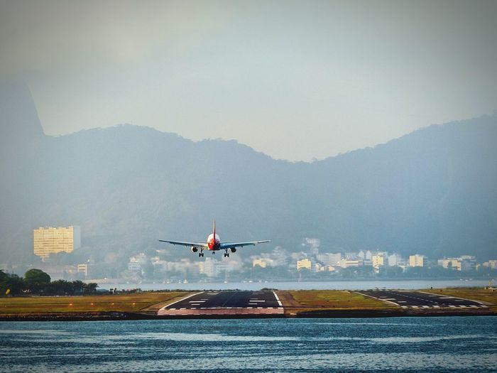 Airplane landing on runway by mountains against sky