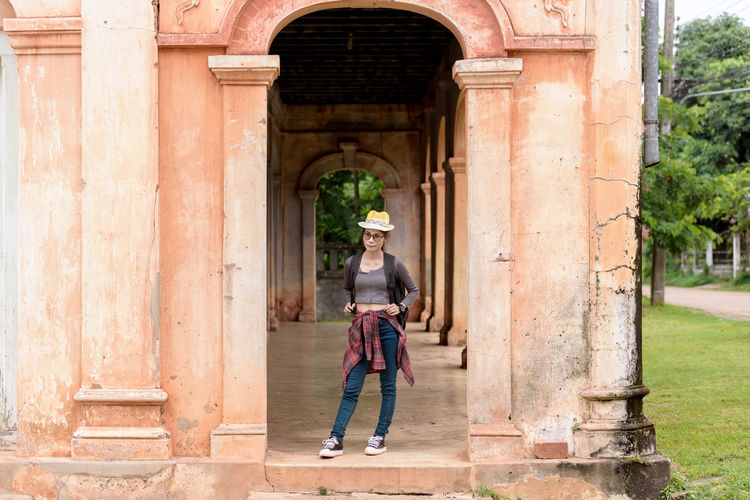 Full length of woman standing at historic building