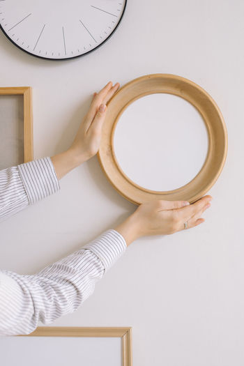 Cropped hand of woman holding picture frame against wall