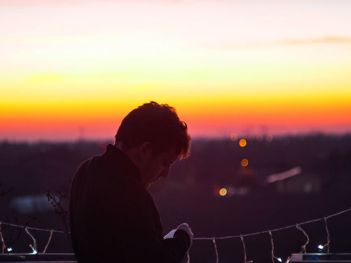 Side view of silhouette young man using smart phone while standing against sky during sunset