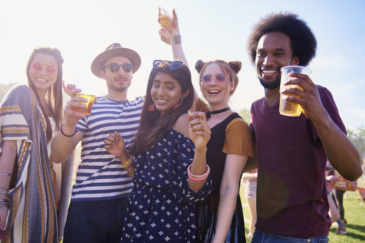 Friends holding drinks in glasses while dancing against sky