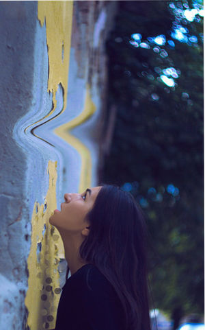 ditch on the wall Adult Beautiful Woman Beauty Black Hair Casual Clothing Contemplation Day Focus On Foreground Hair Hairstyle Leisure Activity Lifestyles Long Hair One Person Portrait Profile View Real People Side View Standing Women Young Adult Young Women