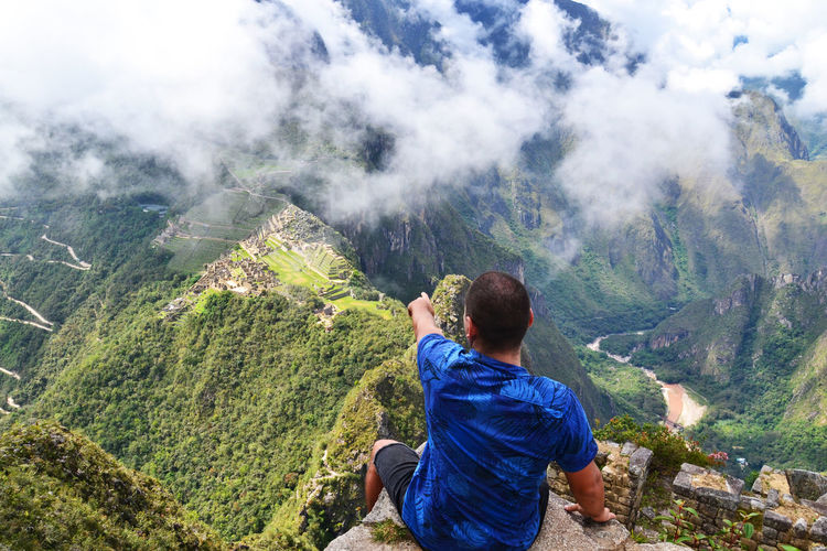 Rear view of sitting on rock while pointing at machu picchu
