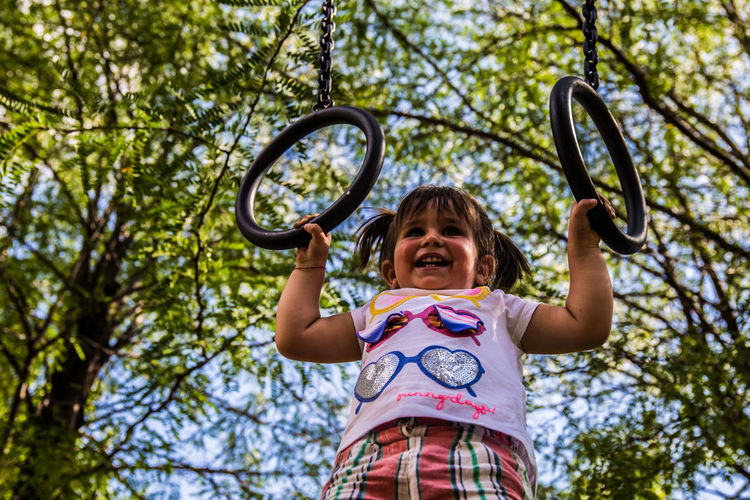 Low angle view of happy girl holding play equipment against trees