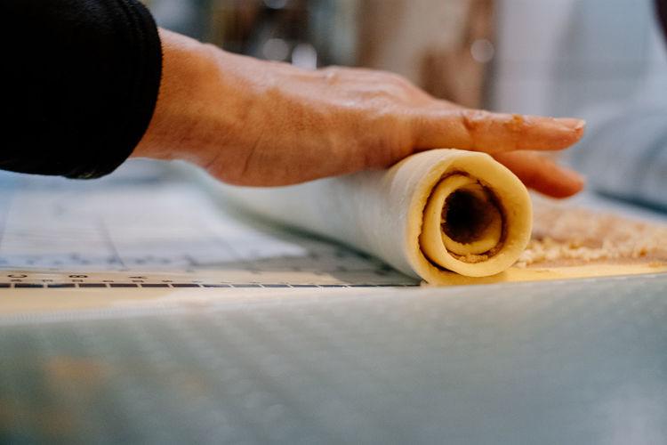 Close up of human hand rolling cake dough