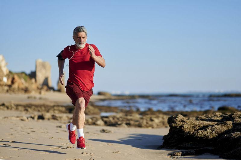 Full length of man running on beach against clear sky