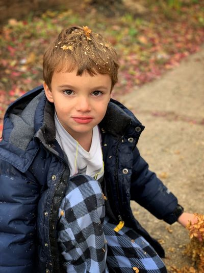Portrait of cute boy sitting outdoors during autumn