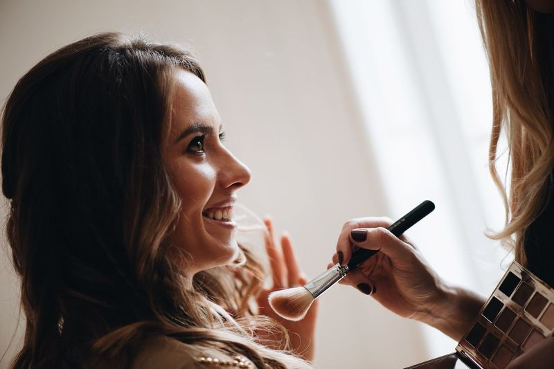 Beautician Applying Make-Up On Face Of Young Woman