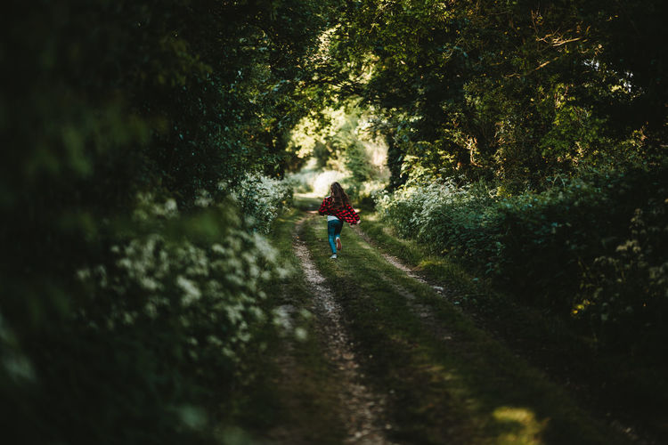 Rear View Of Girl Running On Footpath Amidst Trees