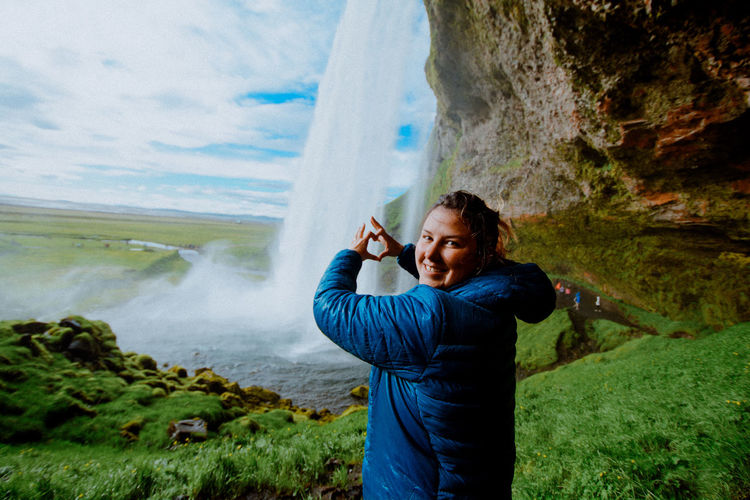 Portrait of smiling woman making heart shape against waterfall
