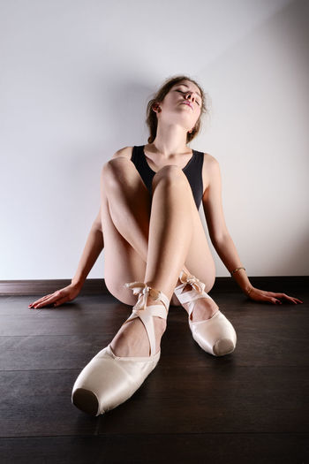 Young woman looking away while sitting on wooden floor